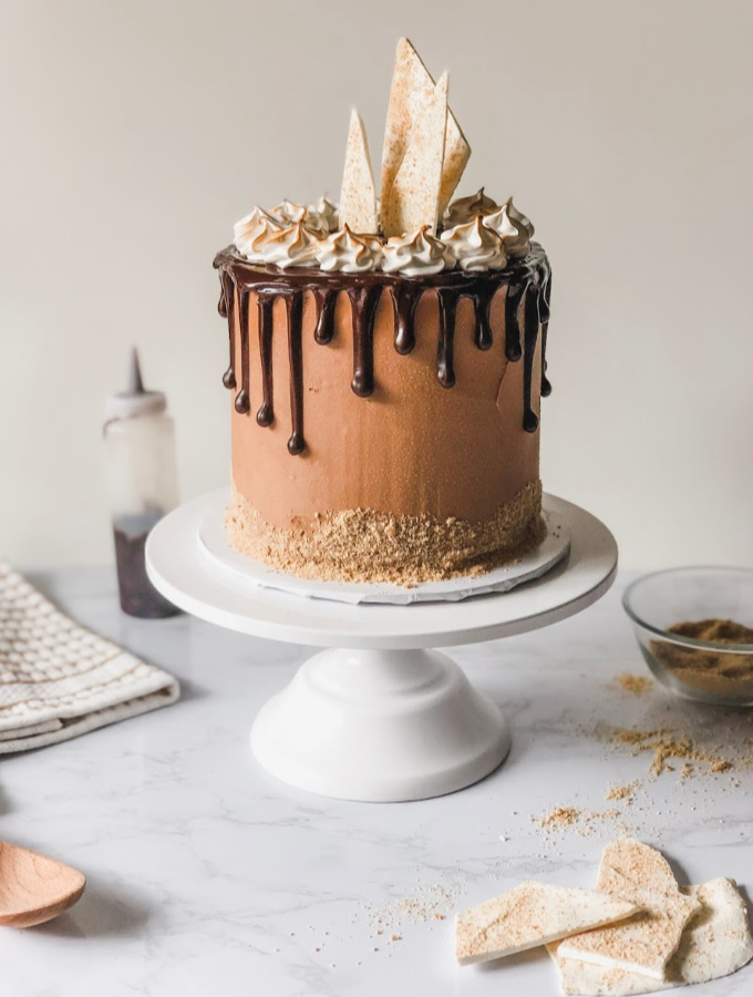 Summer is here, and cravings for ooey-gooey campfire roasted s'mores has begun! This campfire s'mores cake is made from a fluffy homemade vanilla cake with a graham cracker crust layered with creamy milk chocolate buttercream, and toasted marshmallow meringue. This cake has all the flavors of campfire s'mores packed into a delicious dessert.#xokatierosario #smorescake #campfiresmores #marshmallowcake #cakedecorating