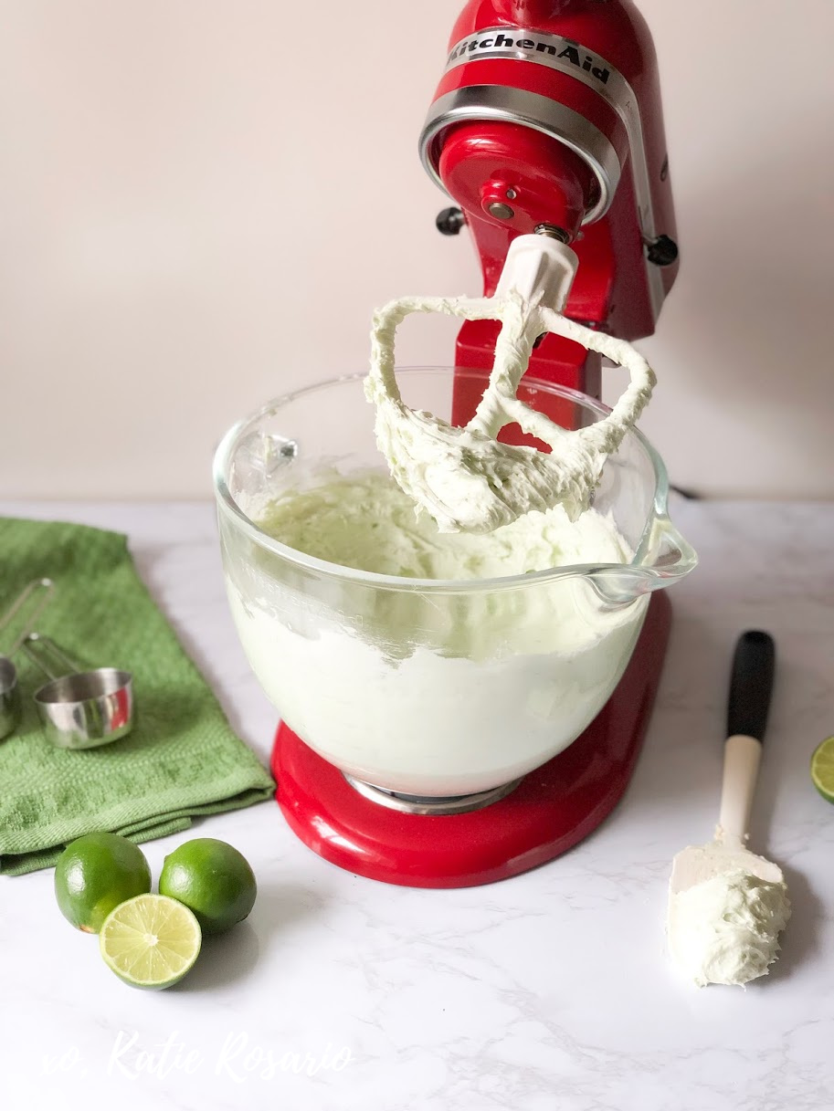 This margarita cake is bold and flavorful which is perfect for those hot summer days. Sweet and decadent lime cake soaked with a tequila syrup, layered with tart lime curd, and creamy tequila lime buttercream. This cake is simple in decoration but doesn't skip on that wonderful homemade flavor. The fresh lime slices and finishing touches of sea salt complete the ultimate margarita. #xokatierosario #margaritacake #tequilalimerecipes #classicmargaritas