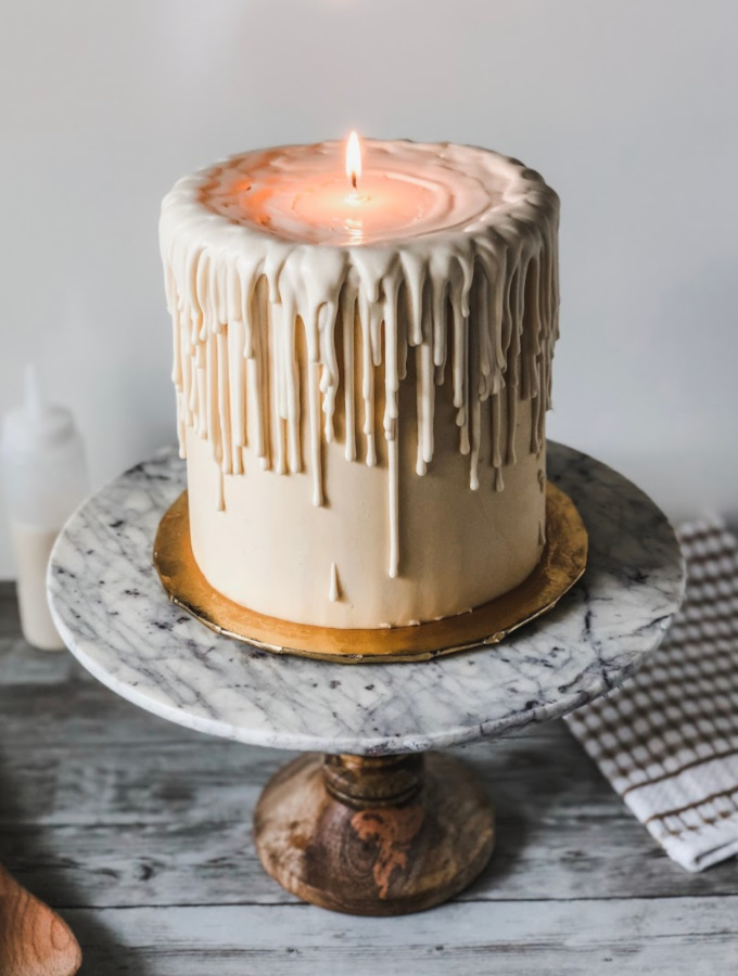 There's no better way to celebrate the holidays than with this super cute cake. This white chocolate melted candle cake has the wow factor to impress your friends and family! The real showstopper for this cake is the ivory chocolate drip; it's made with melted ivory candy melts and warm water. The many layers of white chocolate drip falling down the sides of the cake make this cake everything! #xokatierosario #meltedcandlecake #easyvanillacakerecipe #homemadevanillacake #cakedecoratingtipsandtricks